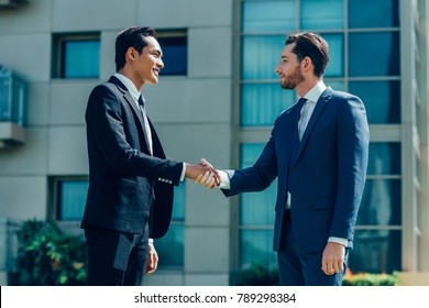 Two Smiling Adult Business Men Shaking Hands