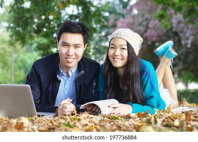 Two smiling asian students lying a the park