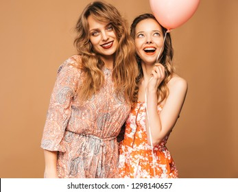Two smiling beautiful women in summer hipster dresses. Girls posing on golden background.Models with colorful air balloons.Having fun, ready for celebration birthday or holiday party