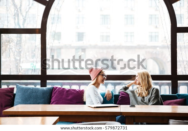 Two smiling beautiful young women talking at the table in cafe