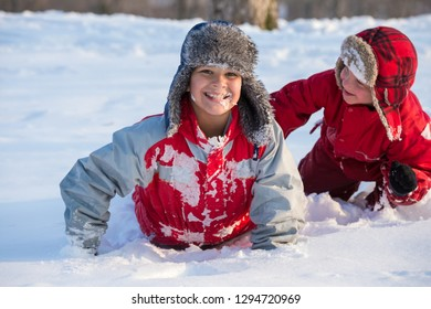 Two smiling boys with funny face in winter clothes playing at the snow at winter park, outdoors