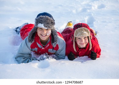 Two smiling boys in winter clothes playing at the snow at winter park, outdoors