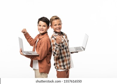 two smiling brothers holding laptops, showing thumbs up and looking at camera isolated on white