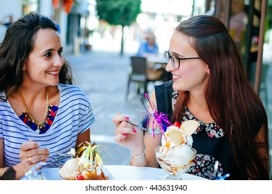 Two smiling brunette girlfriends eating beautiful ice creams from dessert bowl in outdoor cafe