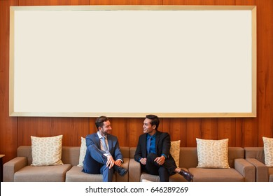 Two Smiling Business Men Chatting in Lounge