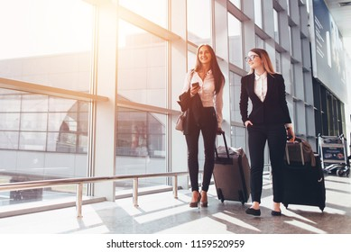 Two smiling business partners going on business trip carrying suitcases while walking through airport passageway