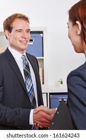 Two smiling business people doing job interview in office after a handshake