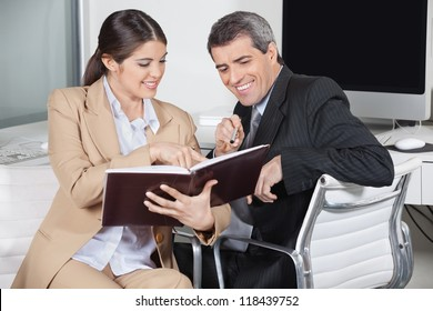 Two smiling business people looking in an appointment book in the office