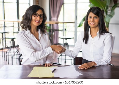 Two smiling business women shaking hands and sitting at table in cafe. They are looking at camera. Business agreement concept. Front view.