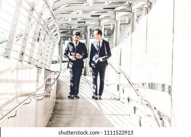 Two smiling businessman coworkers in black suit talking and walking.business people discussing strategy in the modern city