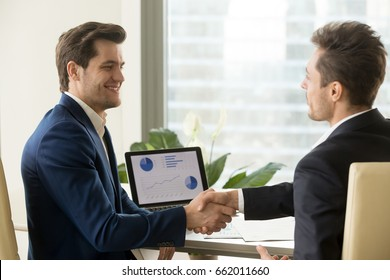 Two smiling businessmen handshaking, sitting at desk with charts graphs on laptop screen, partners shaking hands after successful financial negotiations, satisfied with result, growth, help, support