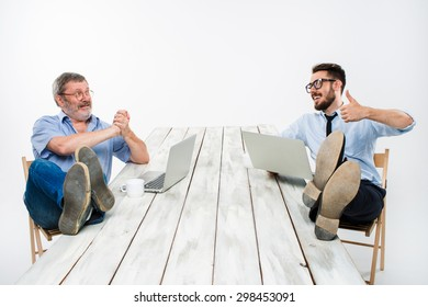 The two smiling businessmen with legs over table working on laptops on white background. Business in the American style - concept understanding