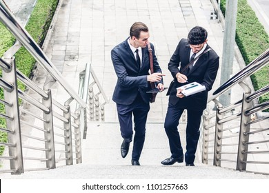 Two smiling businessmen talking and walking in the city