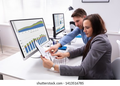 Two Smiling Businesspeople Discussing On Document While Working At Office