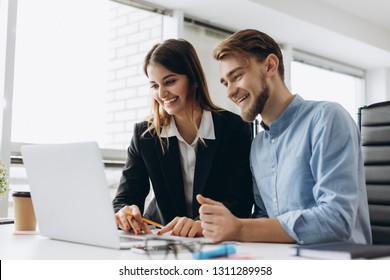 Two smiling businesspeople sitting together at a table in a modern office talking and using a laptop