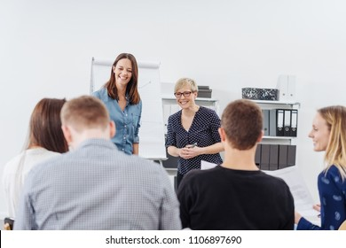 Two smiling businesswomen giving a presentation together or lecturing a group of students at a seminar in a view over the backs of the seated audience