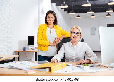 Two smiling businesswomen working together on the computer at the table in office and looking at camera