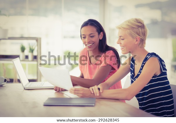 Two smiling businesswomen working together in the office