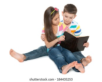Two smiling children read an old book