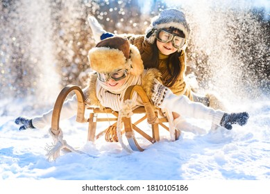 Two smiling children ride lying on a wooden retro sled on a sunny winter day. Active winter outdoors games. Happy Christmas vacation concept.