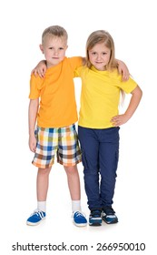 Two smiling children stand together against the white background