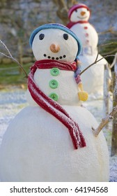 Two smiling Christmas snowmen, with colorfull scarfs and barrets