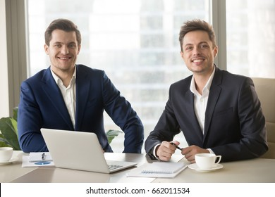 Two smiling confident businessmen looking at camera, financial analysts or investment advisers sitting at office desk with laptop and documents, business analysis, consulting services, team portrait
