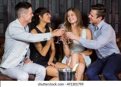 Two smiling couple toasting glasses of champagne at bar