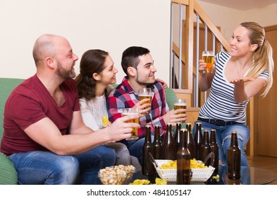 Two smiling couples hanging out with beer and snacks at at house party together