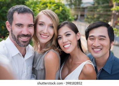 Two smiling couples taking selfie together