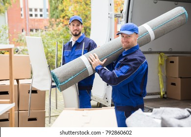 Two Smiling Delivery Men Holding Chairs And Carpet In Front Of Truck