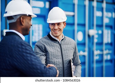 Two smiling engineers wearing hardhats shaking hands together while standing by freight containers in a shipping yard