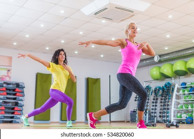 Two smiling female fitness models working out in gym or studio, doing cardio exercise, dancing zumba.