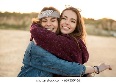 Two smiling female friends hugging each other on the beach