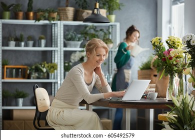 Two smiling florists working in a flower shop