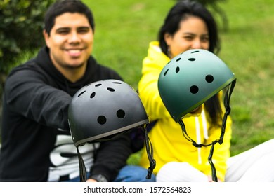 Two smiling friends showing helmet, concept in driving safety with a means of transportation