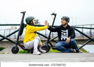 Zwei lächelnde Freunde zeigen Helm, Konzept der Sicherheit beim Fahren mit einem Transportmittel