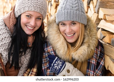 Two smiling friends in winter jackets countryside wooden logs background