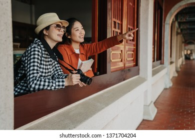 two smiling girls backpackers standing in room in old history monument chinese temple in beijing relying leaning on wooden window. women visitors point finger showing friend discussing style building