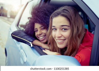 two smiling girls in a car on road trip. young multi-ethnic friends having fun looking out from windscreen on car ride.
