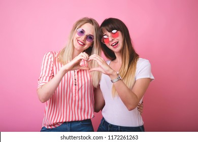 Two smiling girls in dresses showing heart gesture with hands isolated on the pink background.Making heart sign by hands.