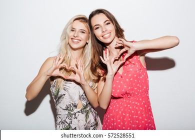 Two smiling girls in dresses showing heart gesture with hands isolated on the white background