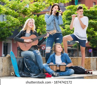 Two smiling girls and two happy boys teenagers friends with musical instruments together outdoors