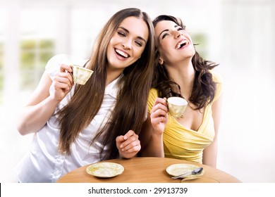 Two smiling girls have coffee time