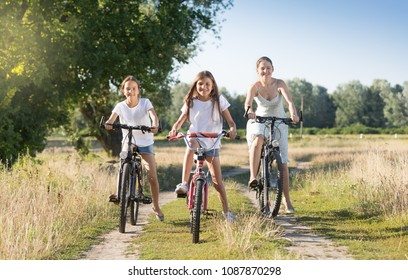 Two smiling girls riding bicycles with young mother on countryside road