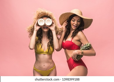 two smiling girls in straw hats holding coconuts and pineapple isolated on pink