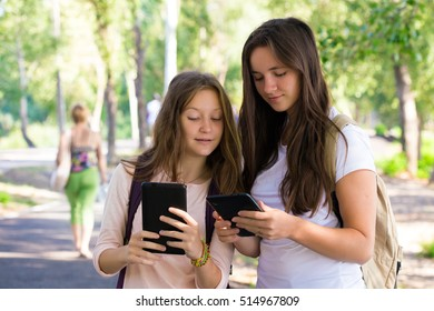 two smiling girls students with the tablets outdoors