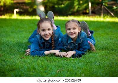 Two smiling girls using tablet while lying on grass at yard