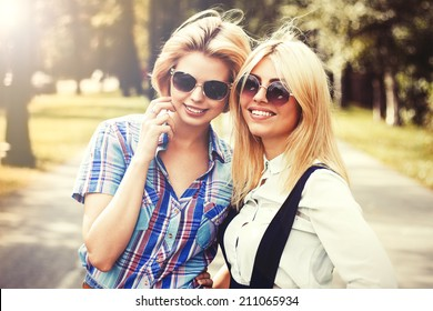 Two smiling girls walking in the park