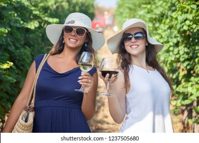 Two smiling girls wine tasting in vineyard and looking at camera. Happy women with wineglasses enjoying a day in nature.